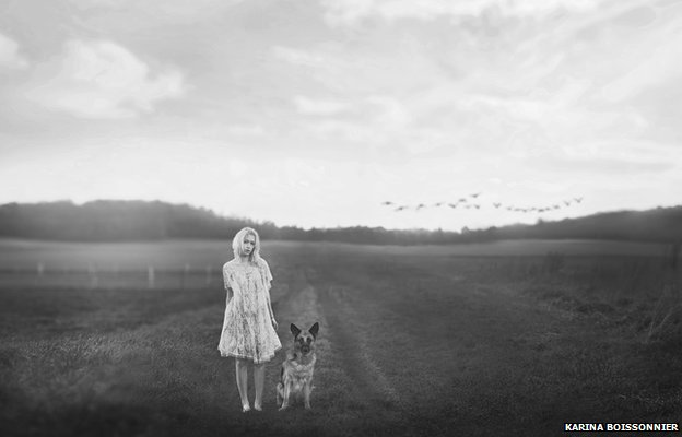 A girl stands barefoot in a field with a German shepherd dog. In the distance a flock of birds flies in formation.