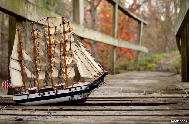 A model of an old-fashioned sailing vessel with full sails and a US flag, is pictured on a bridge in a rural setting.