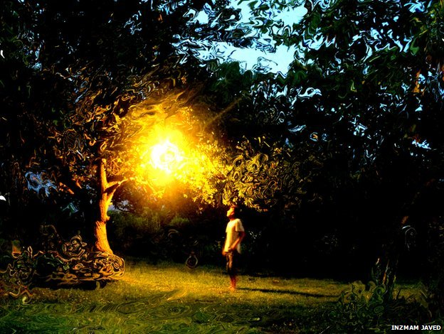 A man stands under a light in a tree-filled garden. A photographic trick creates an impression that the scene is being viewed underwater