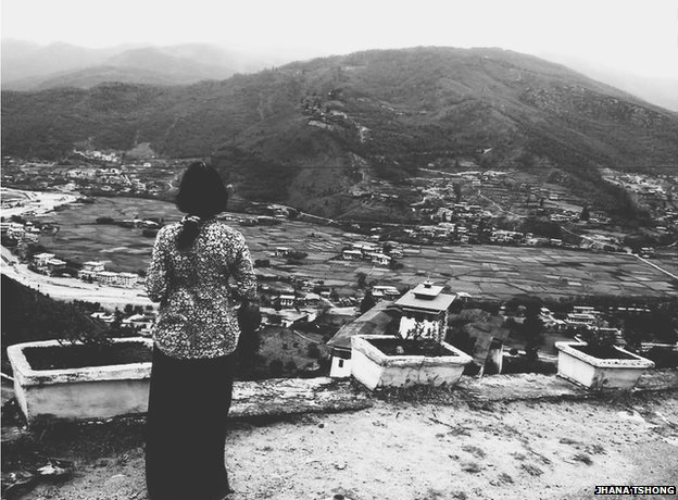 Woman stares out at view of mountain and houses beneath