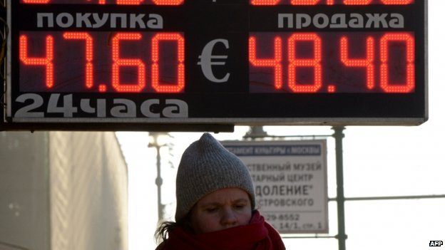 A woman stands under a board listing foreign currency rates against the Russian ruble just outside an exchange office in central Moscow (January 2014)