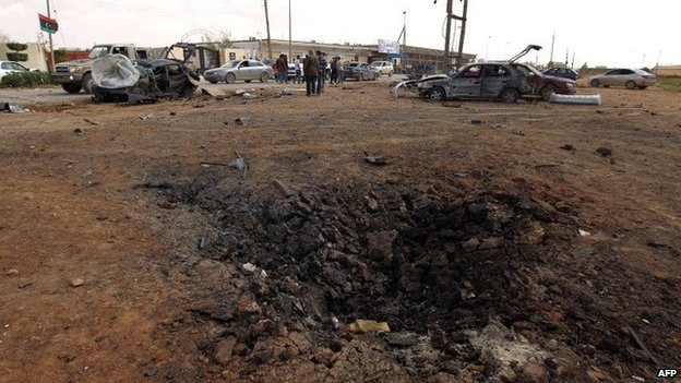 A crater scars the earth after a car bomb targeting a military academy in Libya's restive eastern city of Benghazi detonated on March 17, 2014, killing at least five soldiers and wounded more than 10, military and hospital sources said.