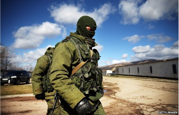 Armed soldiers without identifying insignia keep guard outside of a Ukrainian military base in the town of Perevevalne near the Crimean city of Simferopol on March 17