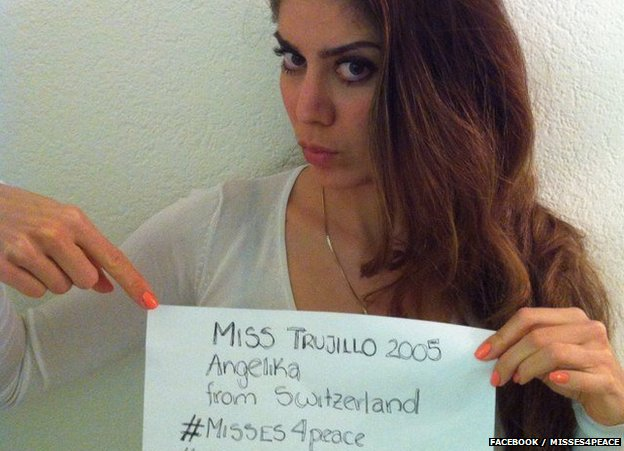 A beauty queen holds up a message of support for the people of Venezuela