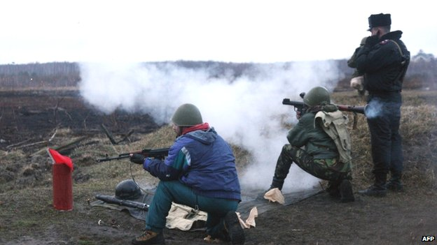 A Ukrainian interim forces officer (right) supervises recruits during a shooting exercise not far from Kiev (17 March 2014)