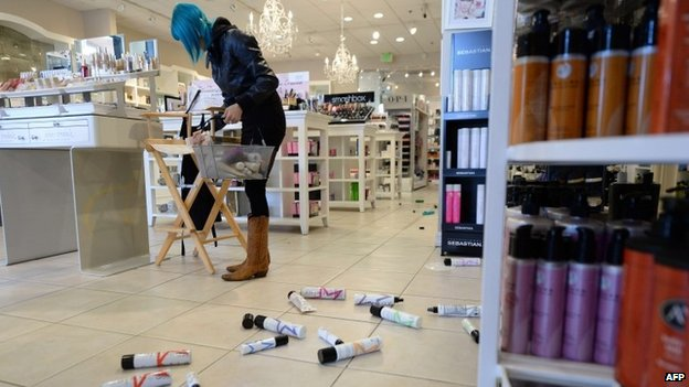 Employee Paula Anania cleans up hair care products that were knocked off the shelf in a beauty supply store in the Encino area of Los Angeles after a 4.4 earthquake jolted the area on 17 March 2014