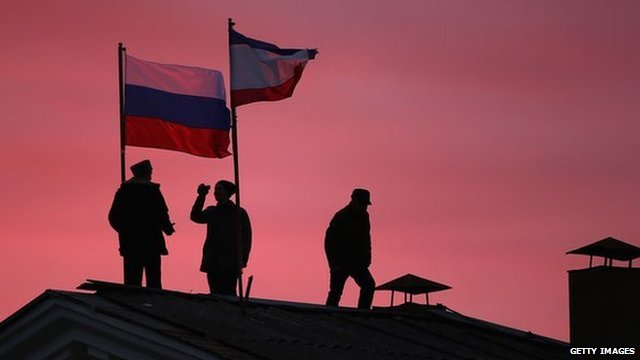 Cossack men install a Russian flag and a Crimean flag on the roof of the City Hall building on 17 March 2014 in Bakhchysarai, Ukraine.