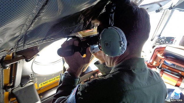 A Royal Australian Air Force crew member of an AP-3C Orion maritime patrol aircraft scans the surface of the sea near the west of Peninsula Malaysia on 17 March 2014