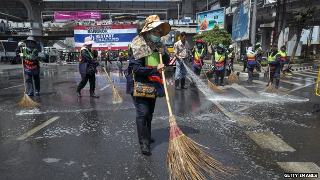 City workers clean the streets at major intersections after anti-government protesters relocated their protest to a central city park on 2 March 2014