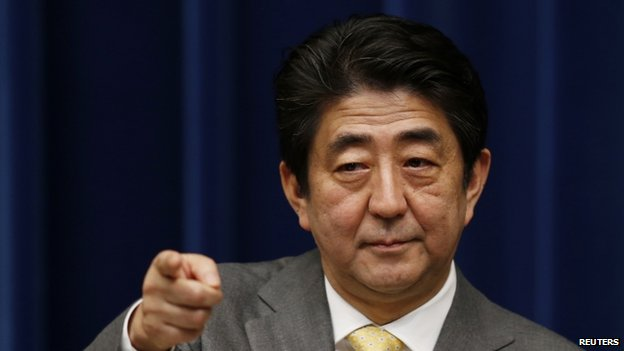 Japan's Prime Minister Shinzo Abe points to a reporter during a news conference at his official residence in Tokyo March 10, 2014, a day before the third anniversary of the 11 March 2011 earthquake, tsunami and nuclear crisis that struck the nations north-east