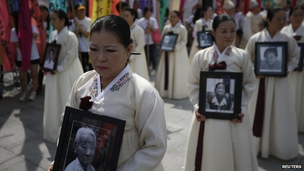Participants carry the portraits of Korean women who were made sex slaves by the Japanese military during World War II, during a requiem ceremony for former comfort woman Lee Yong-nyeo in central Seoul, 14 August  2013
