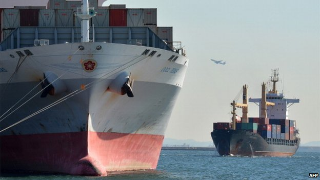 File image of a A T.S. Lines container ship, right, and a Kawasaki Kisen Kaisha Ltd. container ship move through Tokyo Bay in Tokyo, Japan, on Sunday, 18 August 2013
