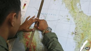 Indonesian Air Force officer with ruler and map plots a flight path