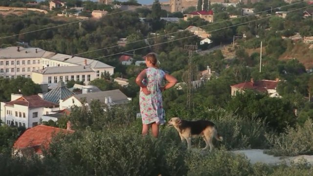 Woman and dog on hillside