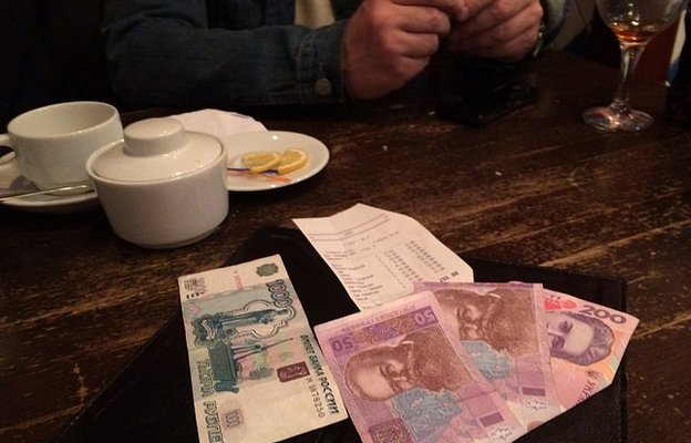 A 1,000-rouble note lies side by side with 300 Ukrainian hryvnya on a restaurant table in Yalta, Crimea. The sums are roughly equivalent