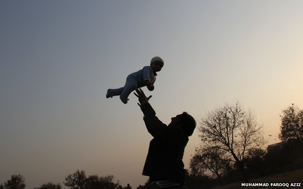 A man plays with a baby, throwing him in the air