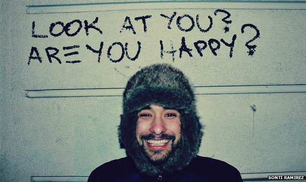 A man smiles under graffiti saying 'Are you happy?'