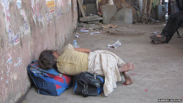 A girl sleeps on a street