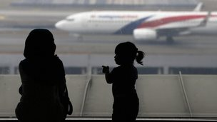 A woman and a girl look at a Malaysia Airlines plane