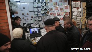 People watch Mr Putin's speech at a stall in Simferopol