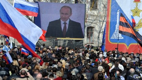 People listen to a speech of Russian president Vladimir Putin broadcast on a giant screen in Sevastopol