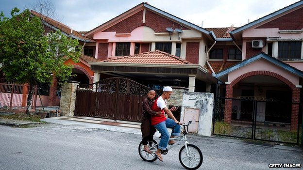 Boys cycle past the house of Fariq Abdul Hamid (16 March 2014)