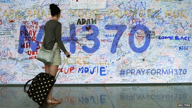 A woman looks at messages of support left for family members and passengers on board the missing Malaysia Airlines Flight MH370 at the Kuala Lumpur International Airport on 18 March 2014
