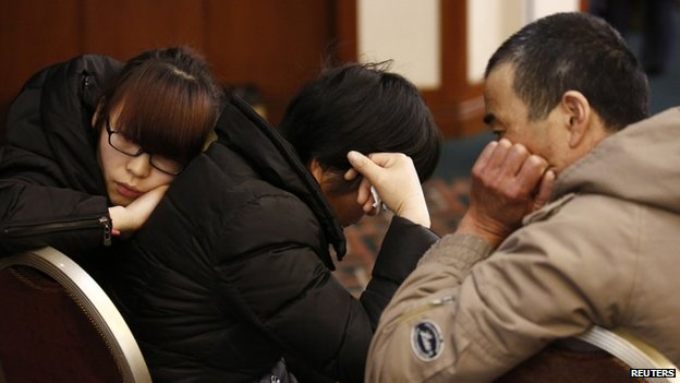 Family members of a passenger onboard the missing Malaysia Airlines flight MH370 react as they listen to a briefing from the airline company at a hotel in Beijing, 18 March 2014