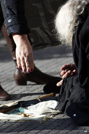 An elderly woman lies on the ground begging for alms in main street on the northern Greek port city of Thessaloniki in 2013