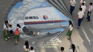 Students stand next to a giant mural featuring missing Malaysia Airlines flight MH370