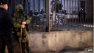 Russian troops outside the Ukrainian Navy headquarters in Simferopol as Ukrainian troops stand guard inside