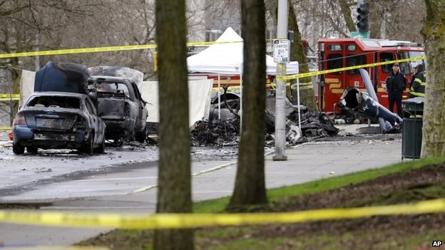 Burned-out vehicles near the wreckage of a news helicopter that crashed in Seattle on 18 March 2014