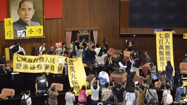Students and protesters hold banners and chairs inside Taiwan's legislature in Taipei on 18 March 2014