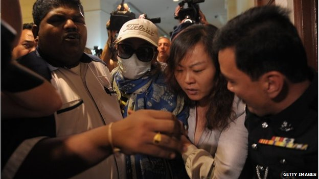 Chinese relatives of passengers from the missing Malaysia Airlines flight MH370 are escorted away by Malaysian police from entering the media centre before the start of a press conference at a hotel near Kuala Lumpur International Airport