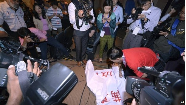 "An official takes away a banner reading (in Chinese) ""We are against the Malaysian government for hiding the truth and delaying the rescue. Release our families unconditionally!"""