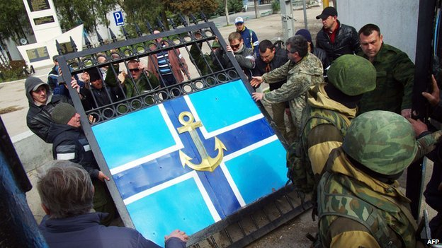 Pro-Russian protesters remove the gate of Ukraine's navy HQ in Crimea on 19 March 2014