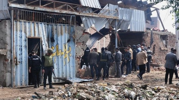 Egyptian security forces inspect a warehouse in Qalyubiya province raided on 19 March 2014