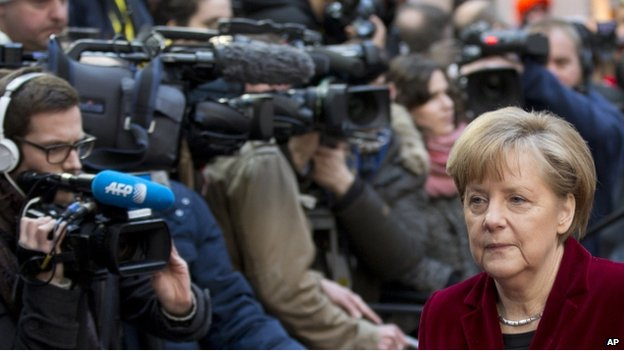 German Chancellor Angela Merkel walks past reporters