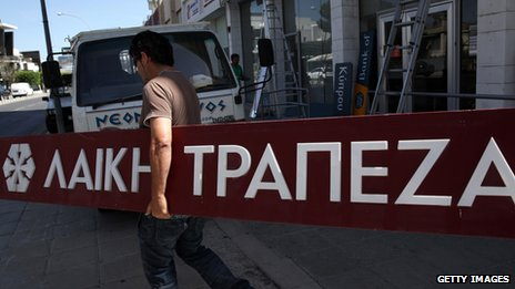 Worker carrying a Laiki Bank sign, in May 2013