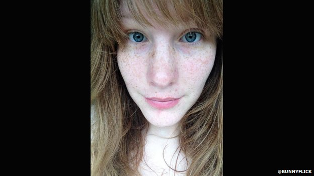 A woman wearing no makeup takes a selfie