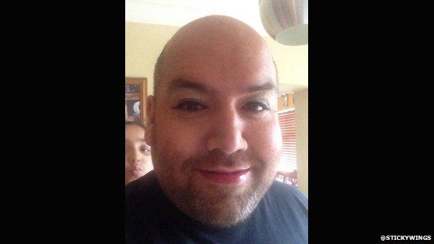 A man wearing makeup takes a selfie