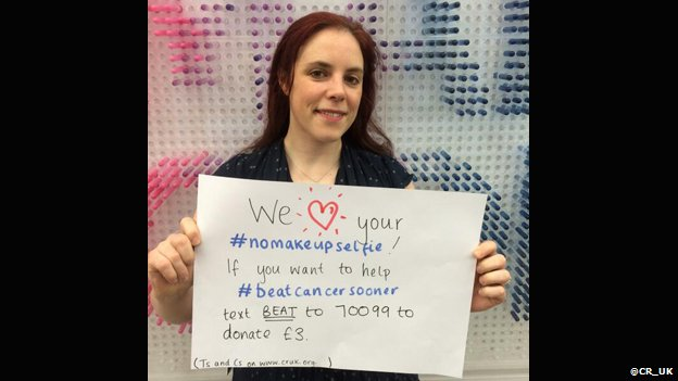 A woman holding a sign asking for donations for Cancer Research