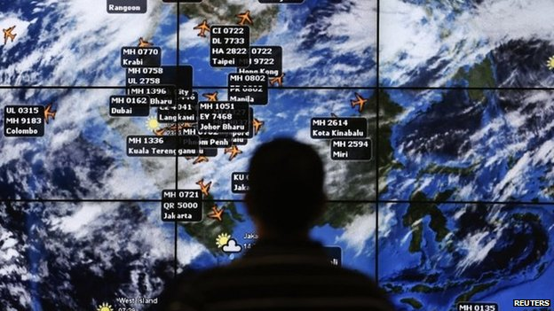 A man watches a large screen showing different flights at the departure hall of Kuala Lumpur International Airport 13 March 2014