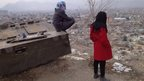 Girls with skateboards look out over Kabul
