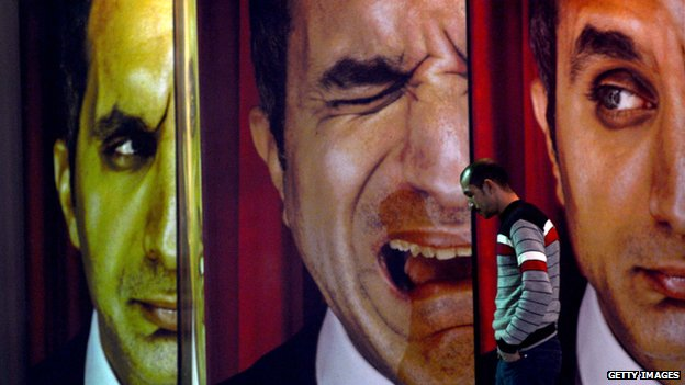 An Egyptian walks past posters of Egyptian satirist Bassem Youssef