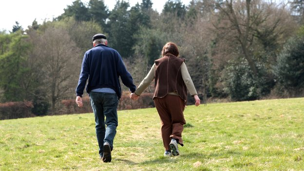 A middle-aged couple walk in the woods