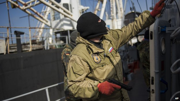 A pro-Russia forces man holds a gun during seizure of the Ukrainian corvette Khmelnitsky in Sevastopol, Crimea (March 20, 2014)
