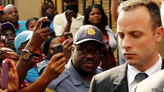 Oscar Pistorius is escorted out of the Pretoria courtroom on day 12 of his trial