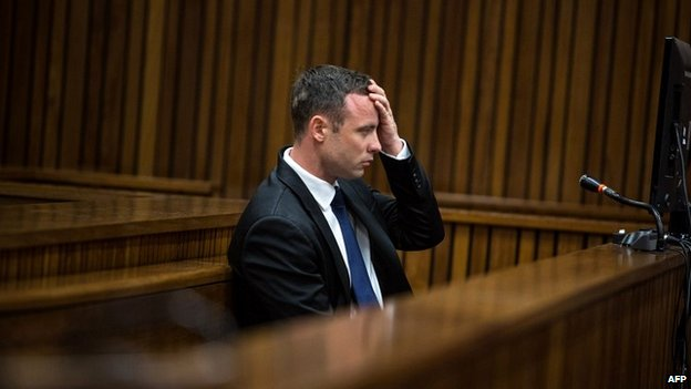 Oscar Pistorius holds his hand to his head during evidence on day 11