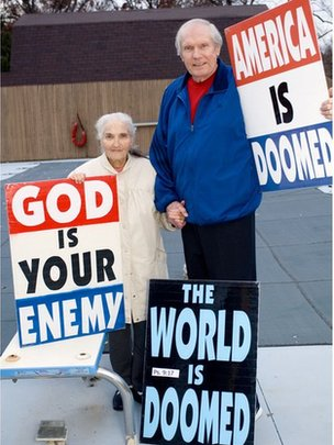 Phelps, shown with his wife and some of his signs, in 2007